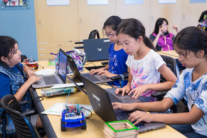 Four female middle school students in summer robotics academy are gathered around a desk. All four students are sitting in front of laptops and writing code for their robots.